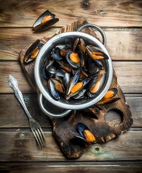 Świeże owoce morza małże na patelni na drewnianym stole.