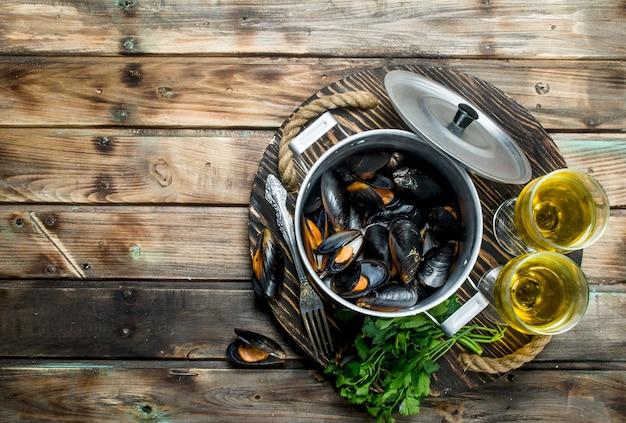Świeże owoce morza małże w garnku białego wina na drewnianym stole.