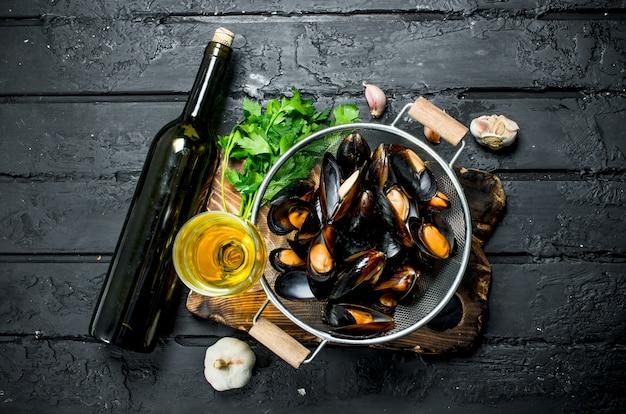 Świeże owoce morza małże z białym winem i pietruszką na czarnym drewnianym stole