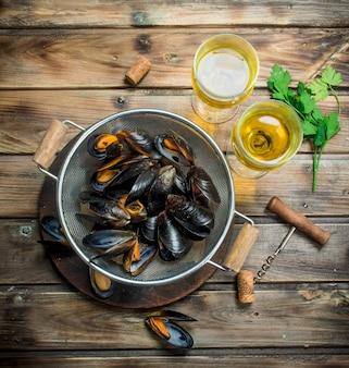 Świeże owoce morza małże z białym winem na drewnianym stole.