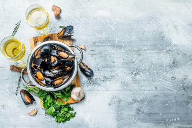 Świeże owoce morza małże z pietruszką i białym winem na drewnianym stole