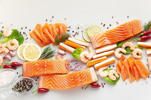 Świeże owoce morza na stole z przyprawami, warzywami i oliwą z oliwek: świeży i wędzony łosoś, krewetki i paluszki krabowe do supermarketu lub restauracji rybnej sushi.