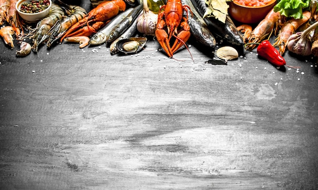 Świeże owoce morza szeroka gama krewetek, homarów, ośmiornic i innych organizmów morskich na czarnej tablicy