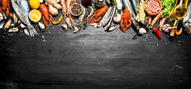 Świeże owoce morza. szeroka gama krewetek, homarów, ośmiornic i innych organizmów morskich na czarnej tablicy.