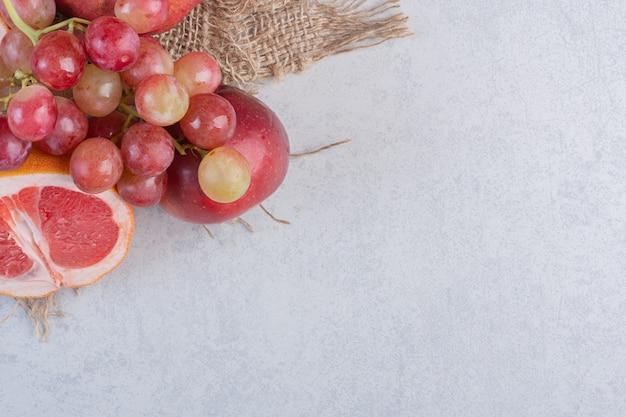 Świeże owoce organiczne. jabłko, winogrona i mandarynki na szarym tle.
