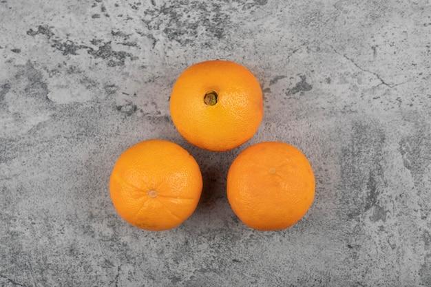 Świeże owoce pomarańczowe na białym tle na kamiennym stole.