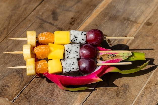 Świeże owoce tropikalne na szaszłykach w owocach smoka
