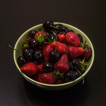 Świeże owoce truskawek i wiśni w filiżance