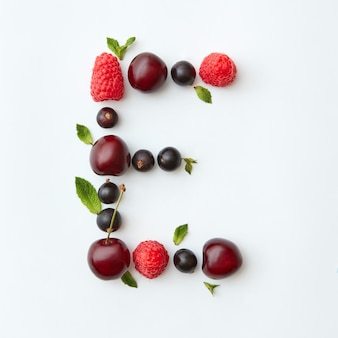 Świeże owoce wzór litery e alfabetu angielskiego z naturalnych dojrzałych jagód - czarna porzeczka