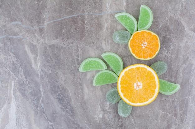 Świeże owoce ze słodkimi marmoladami na tle marmuru.