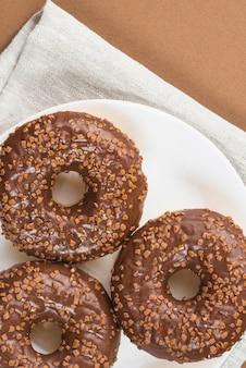 Świeże pączki z czekoladą i posypką na talerzu