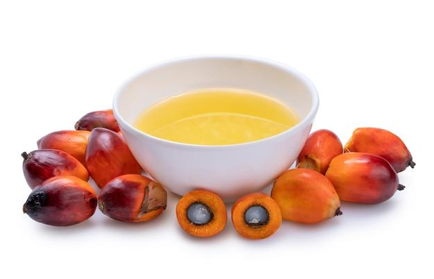 Świeże palmy olejowe i olej palmowy do gotowania na białym tle na białej powierzchni