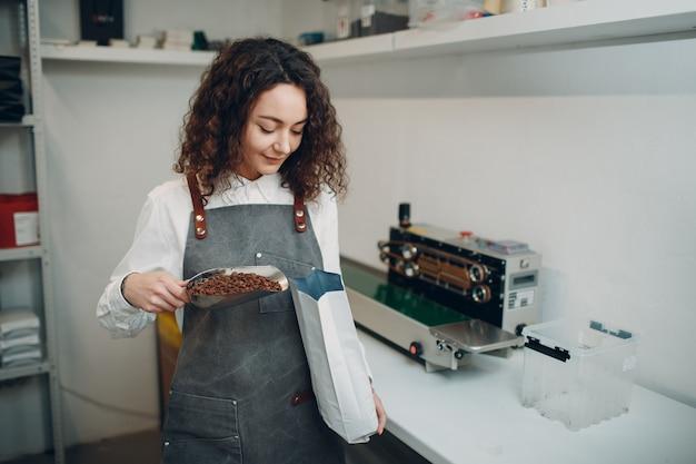 Świeże palone ziarna kawy młody pracownik kobieta pakująca maszyna w szczelnie zamkniętej torebce próżniowej