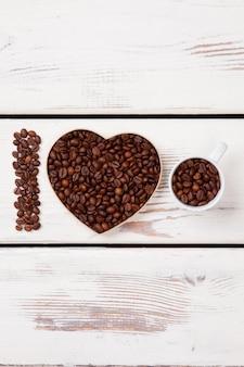 Świeże palone ziarna kawy ułożone w formy. litera i w kształcie serca i kubek wypełniony fasolą. powierzchnia białego drewna.