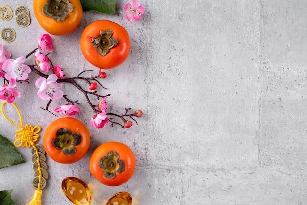 Świeże persymony na szarym tle stołu do projektowania owoców chińskiego nowego roku, słowa na złotej monecie oznaczają nazwę dynastii, którą stworzyła.