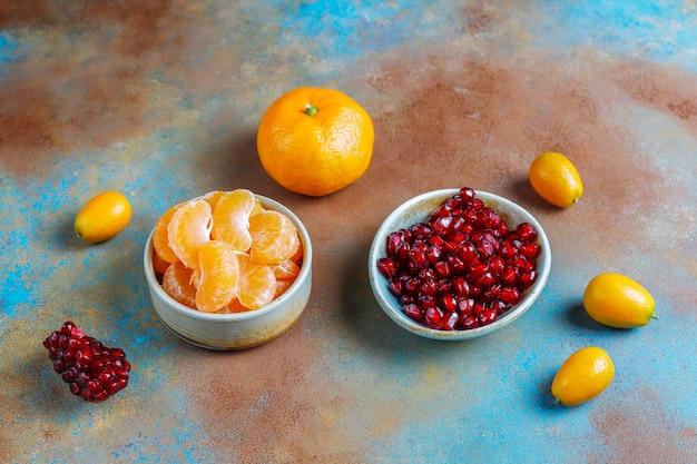 Świeże pestki granatu, plasterki mandarynki i owoce kumkwatu.