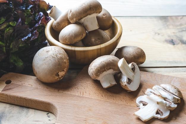 Świeże pieczarki w drewnianym pucharze na stole