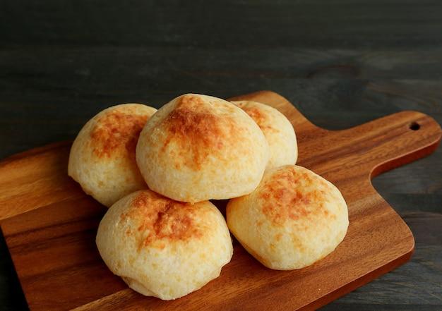 Świeże pieczone domowe brazylijskie chleby serowe lub pao de queijo na drewnianej desce do krojenia chleba