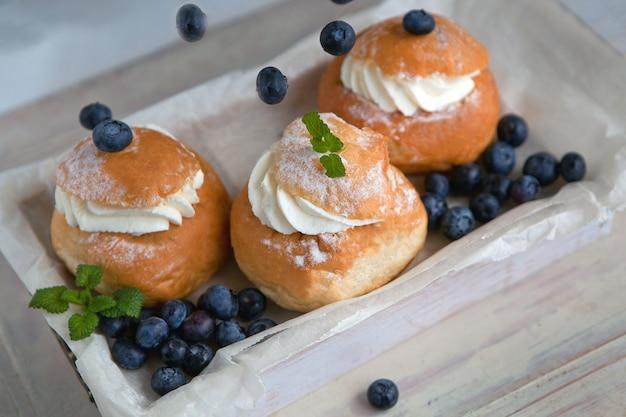 Świeże pieczone domowe bułki z jeżynami na stole na śniadanie pieczenie tradycyjnego szwedzkiego chleba semla dla throve w czwartek. koncepcja jedzenia