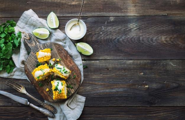 Świeże pieczone kolby kukurydzy z sosem aioli i kolendrą na rustykalnym drewnianym tle