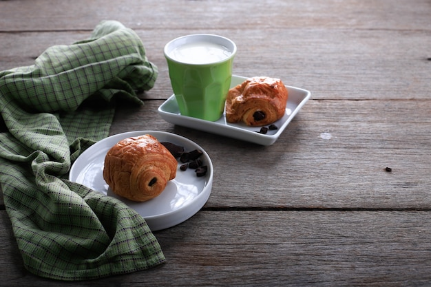Świeże Pieczone Rogaliki Czekoladowe (pain Au Chocolat) Z Mlekiem Na śniadanie. Podawane Na Białym Talerzu Na Rustykalnym Stole Miejsce Na Tekst Premium Zdjęcia