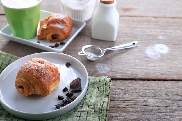 Świeże pieczone rogaliki czekoladowe (pain au chocolat) z mlekiem na śniadanie. podawane na białym talerzu na rustykalnym stole miejsce na tekst