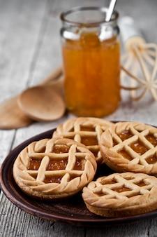 Świeże pieczone tarty z nadzieniem dżem marmoladowy lub morelowy i na płytce ceramicznej i naczyniu piekarniczym kuchni.