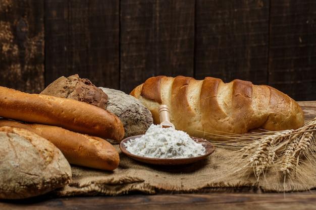 Świeże pieczywo chrupiące z mąką na drewnianym stole