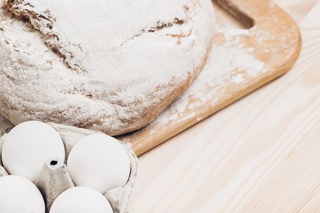Świeże pieczywo, mąka i jajka na drewnianym stole. miękkie światło