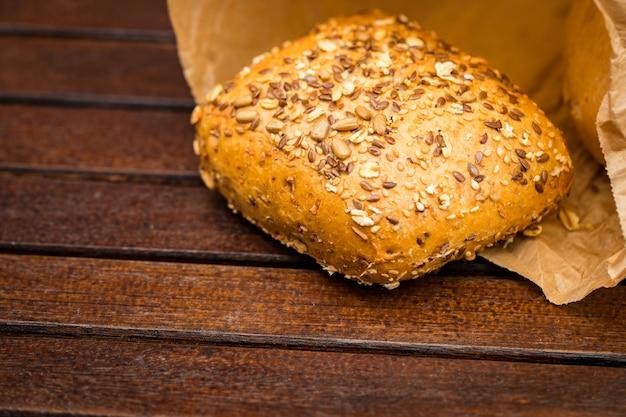 Świeże pieczywo owinięte w papier, na drewnianym tle.