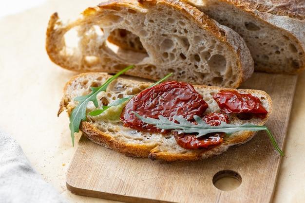 Świeże pieczywo z suszonymi pomidorami i rukolą. zdrowy i pyszny lunch, wegańskie menu, owoce i warzywa. piekarnia, świeże pieczywo wypiekane w domu lub w cukierni