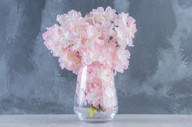 Świeże, piękne kwiaty zapachowe w dzbanku, na białym stole.