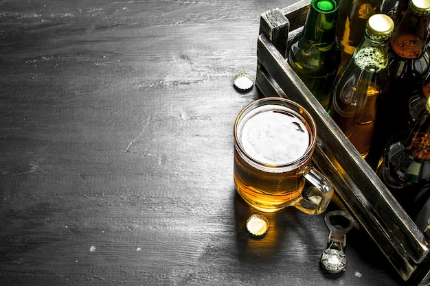Świeże piwo w starym pudełku na czarnej tablicy