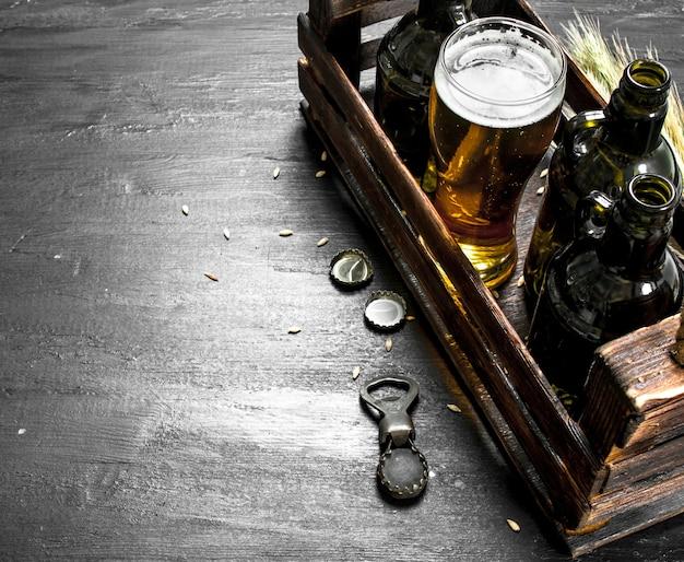 Świeże piwo w szkłach iw starym pudełku. na czarnej tablicy.