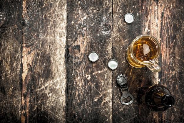 Świeże piwo w szklance z korkami i otwieraczem do butelek na drewnianym stole.