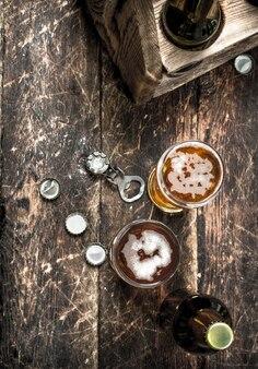 Świeże piwo w szklance z korkami i otwieraczem do butelek na drewnianym tle