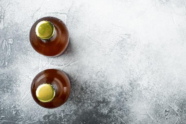 Świeże piwo w szklanych butelkach ustawione na szarym kamiennym stole, widok z góry na płasko