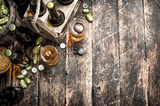Świeże piwo z zielonym chmielem i słodem na drewnianym stole.