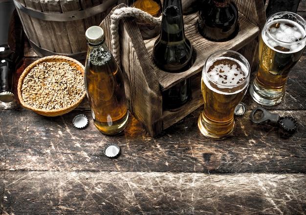 Świeże piwo z zielonym chmielem i słodem. na drewnianym tle.