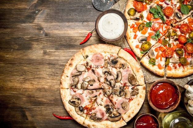 Świeże pizze z kiełbasą i warzywami.