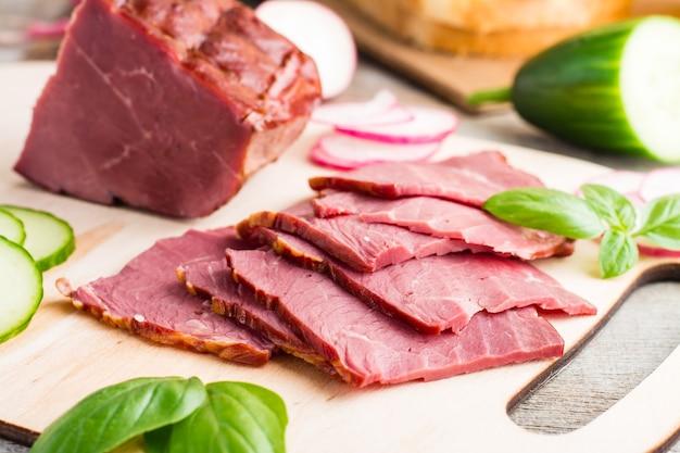 Świeże plasterki marmurkowej wołowiny pastrami i warzywa na desce do krojenia. amerykański przysmak. styl rustykalny. zbliżenie