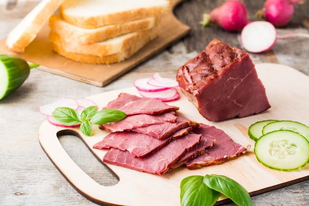 Świeże plasterki marmurkowej wołowiny pastrami i warzywa na desce do krojenia. amerykański przysmak. styl rustykalny.