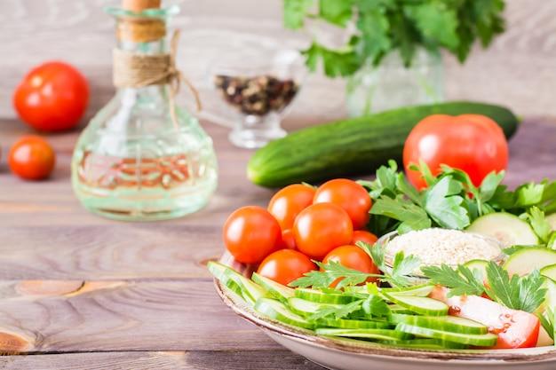 Świeże plastry ogórków, pomidorów, sezamu w misce i natka pietruszki na talerzu na drewnianym stole. olej i przyprawy do gotowania sałatek warzywnych