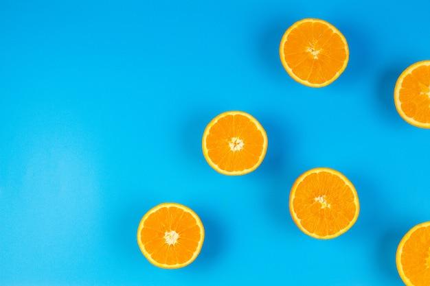 Świeże plastry pomarańczy odizolowane na niebiesko