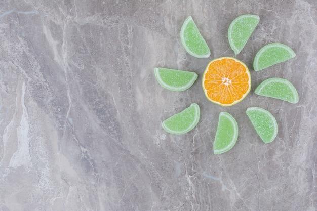 Świeże plastry pomarańczy ze słodkimi marmoladami na tle marmuru.