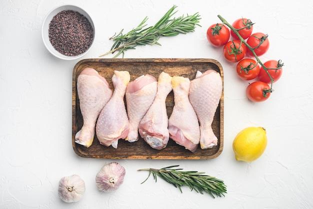 Świeże podudzia z kurczaka, nogi z dodatkami do zestawu do gotowania, rozmaryn, przyprawy i warzywa, na białym stole, widok z góry na płasko