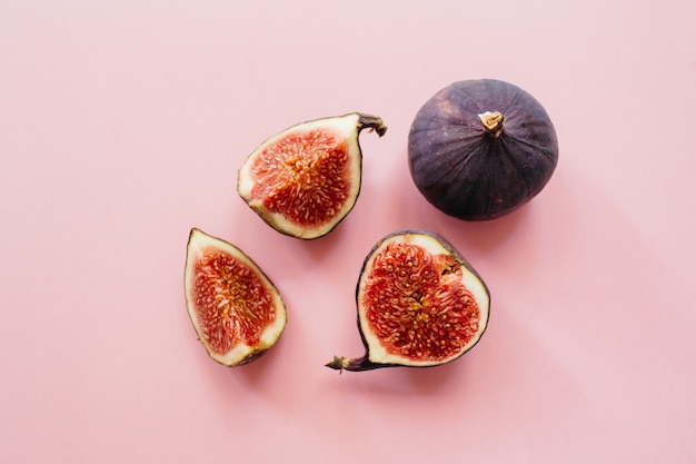 Świeże pokrojone i całe dojrzałe figi na różowym tle. tło zdjęcie żywności. leżał płasko, widok z góry. skopiuj miejsce.