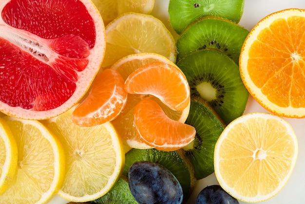Świeże pokrojone owoce i cytrusy na białym tle