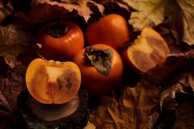 Świeże pokrojone persimmon owoc w pomarańczowych jesień liściach na drewnie
