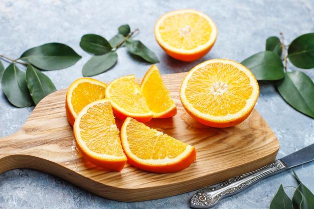 Świeże pokrojone pomarańcze na desce do krojenia na powierzchni betonu